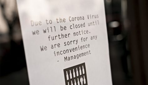 A sign alerts bar customers that it is closed due to Coronavirus