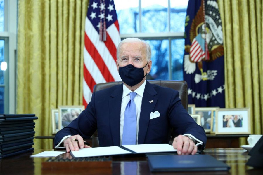 President Joe Biden signs executive orders in the Oval Office after his inauguration.