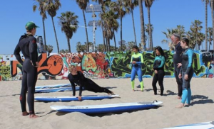 Image of Aloha Brothers surf instructors teaching some skills on the sand before heading into the ocean.